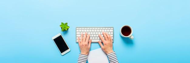 Женщина работает в офисе на синем фоне. концепция рабочего пространства, работа за компьютером, внештатный сотрудник. баннер