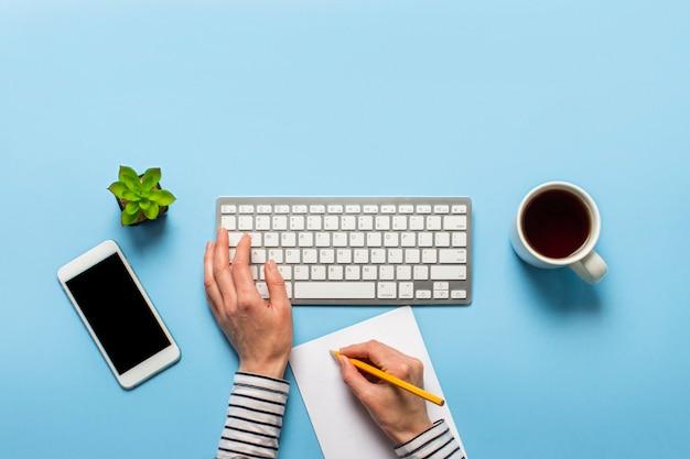 女性は、青色の背景にオフィスで働いています。