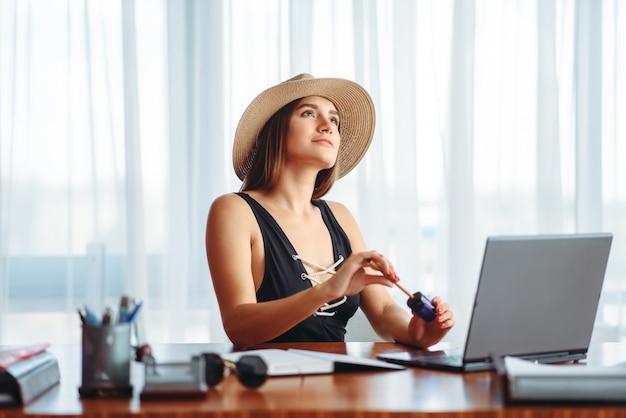 Женщина работает на ноутбуке и мечтает об отпуске