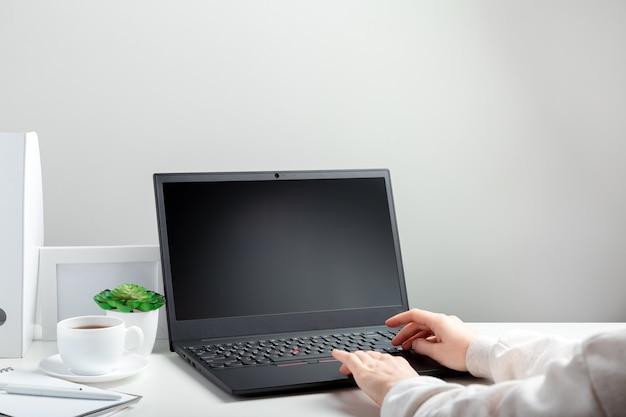 Женщина работает на ноутбуке в онлайн-образовании на белом рабочем месте. женские руки, набрав на ноутбуке. черный дисплей ноутбука пустой макет. рабочее место в домашнем офисе для удаленной работы в стиле минимализма.