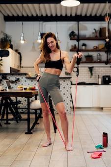 女性は自宅で運動しますレジスタンスバンド上腕二頭筋カール。