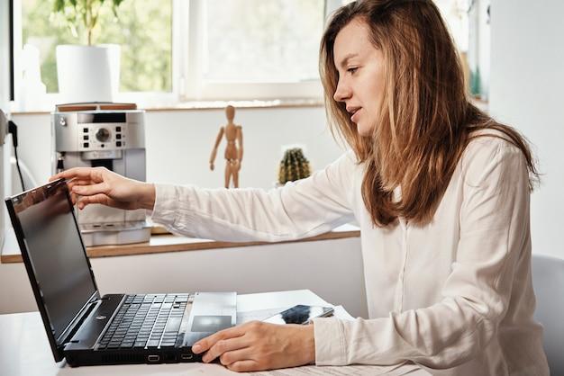 Женщина работает удаленно в домашнем офисе с ноутбуком