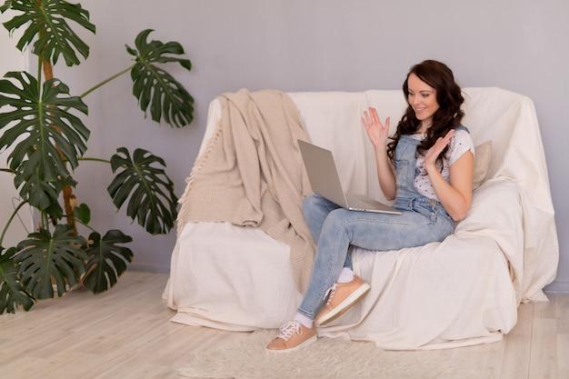 女性はラップトップで自宅からリモートで働きます。遠隔学習とオンライン作業。