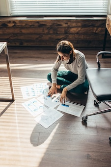 Женщина работает, сидя на полу с официальными документами. самоизоляция и работа дома.