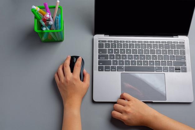 La donna lavora con un laptop a casa e tiene un mouse del computer nella mano sinistra.