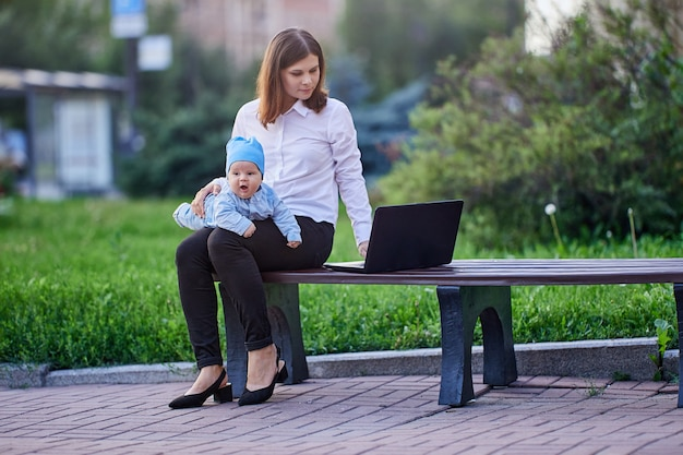 Woman works with laptop with infant on knees outdoors