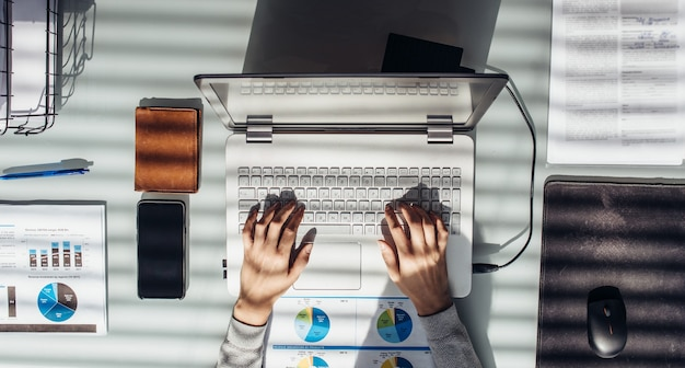 Woman works with laptop at work table.