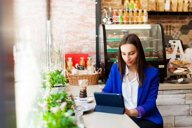 Woman works with a tablet at the table in a cafe
