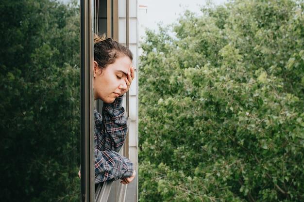 春の日の街の窓を見せびらかしながら心配している女性、メンタルヘルスのコンセプト