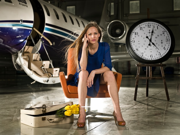 Woman would be seated at an airport with a clock beside