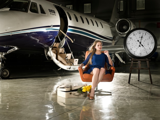 Woman would be seated at an airport with a clock by the side and a suitcase