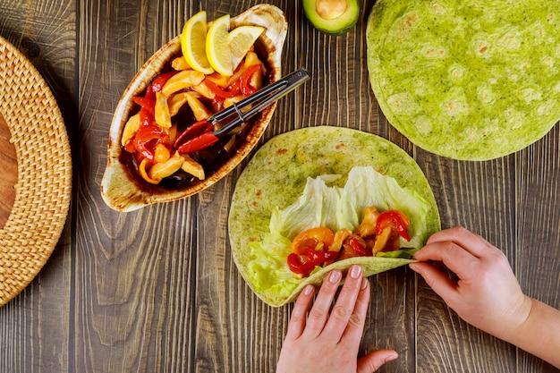 Женщина оборачивает жареную курицу с овощами в лаваш