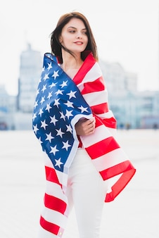 Woman wrapped in american flag patriotically looking along square
