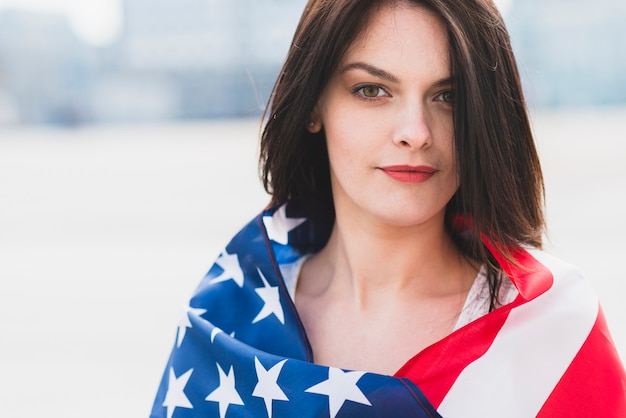 Woman wrapped in american flag patriotically looking at camera