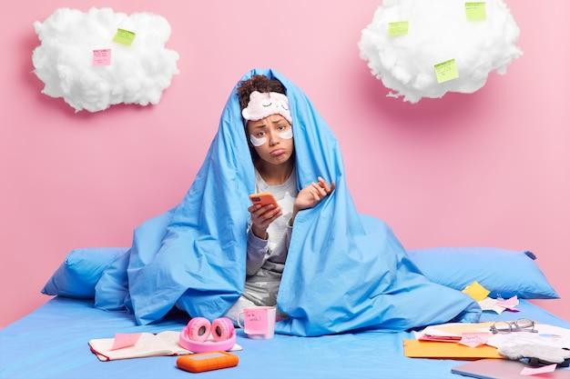 Donna avvolta in una coperta attende la chiamata tiene lo smartphone indossa il pigiama e i cerotti di bellezza sotto gli occhi lavora da casa ha molti compiti da fare su un letto comodo