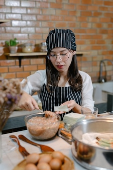 Woman wrapped in dumplings asian food cook.