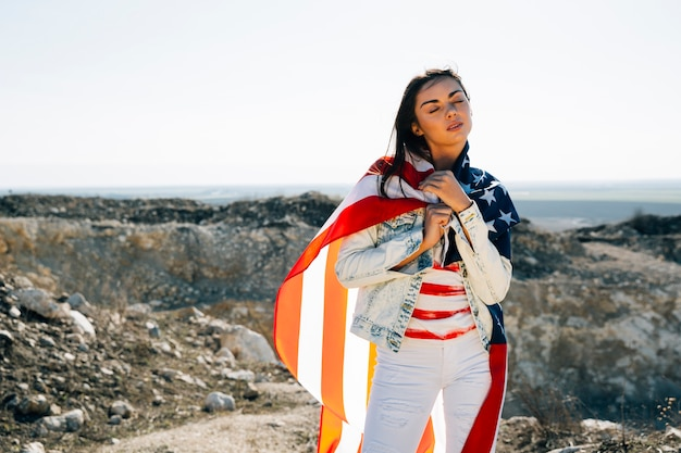 Woman wrapped in flag standing on mountain