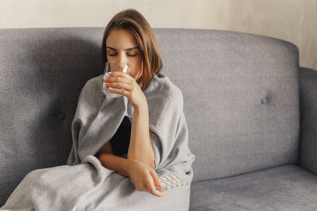 A woman wrapped in a grey blanket holding pills and drinking water, freezing, sitting on the sofa, at home.