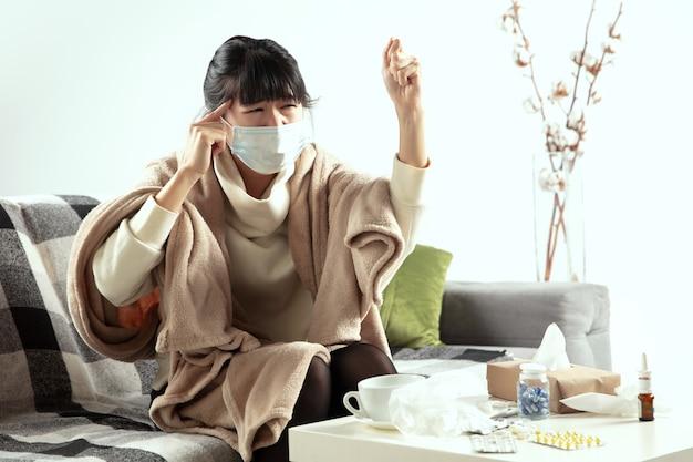 Женщина, завернутая в плед и одетая в маску, пытается защитить себя от больных рядом
