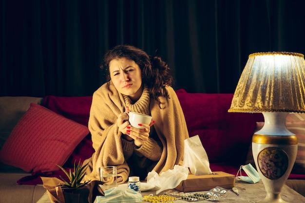 Женщина, завернутая в плед, выглядит больной, чихает и кашляет, сидя дома в помещении