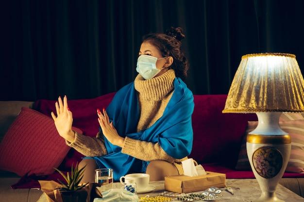 누군가의 아픈 사람으로부터 자신을 보호하기 위해 안면 마스크를 쓴 격자 무늬에 싸인 여성은 집에 있는 소파에 앉아 당황하고, 화나고, 슬퍼 보입니다. 건강 관리 및 의학, 질병 예방.