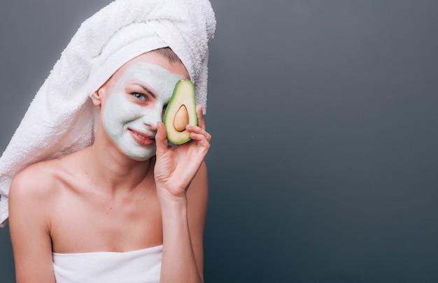 Женщина завернута в полотенце с косметической маской на лице и авокадо в руках