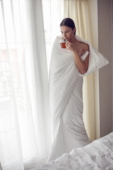 Женщина, закутанная в белое одеяло, стоит у большого окна, занавески пьет чай из кружки, греясь от холода после ванны.