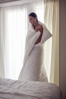 Женщина, закутанная в белое одеяло, стоит у большого окна с занавесками, греясь от холода после ванны.