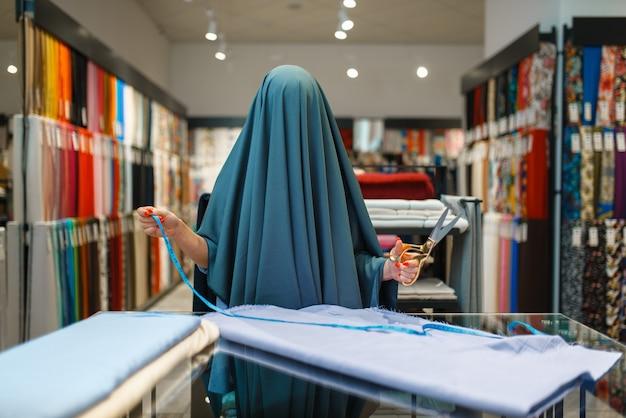 Женщина, завернутая в ткань, текстильный магазин. швея выбирает материал для шитья, портниха в магазине, портниха