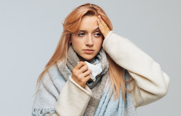 Woman wrapped in scarf, having flu symptom, touching her forehead, uses napkin, isolated