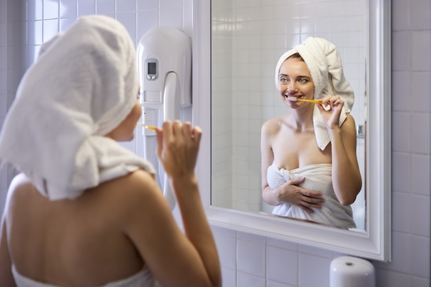 Woman wrapped in towel brushes her teeth in front of bathroom mirror