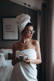 Woman wrapped in a towel drinking coffee