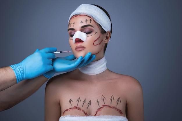 붕대와 흉터로 싸인 여성은 또 다른 수술을 준비합니다.