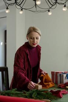 현대적인 방식으로 집에서 친환경 옷으로 크리스마스 선물을 포장하는 여자