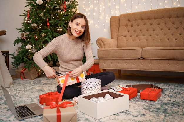 Woman wrapping christmas gift while sitting on the carped in the living room