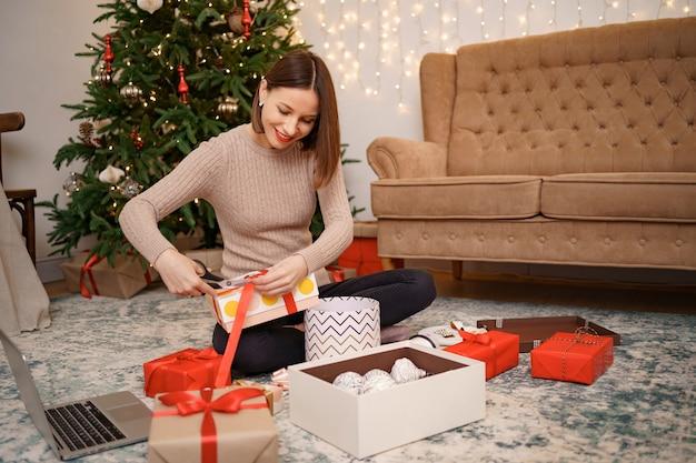 거실에 carped에 앉아있는 동안 크리스마스 선물을 포장하는 여자