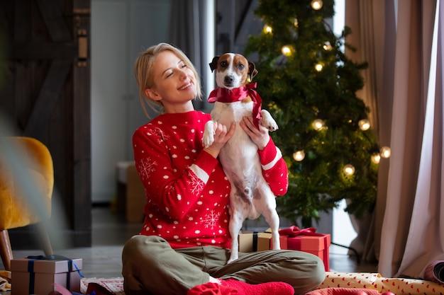 집에서 바닥에 크리스마스 선물을 포장하는 여자.