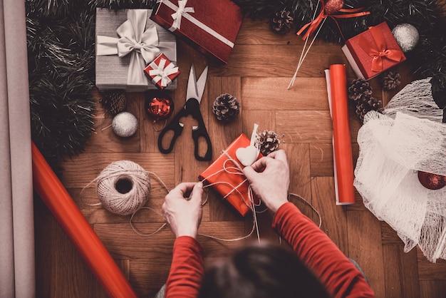 Женщина, упаковывающая рождественские подарки дома