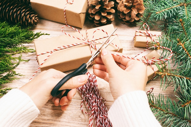 Woman wrapping christmas present , girl prepares xmas gifts with fir tree and pine cone. hand crafted gift on wooden  with christmas decor. top view, copyspace. toned