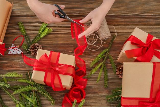 Женщина, упаковка подарка на рождество за столом