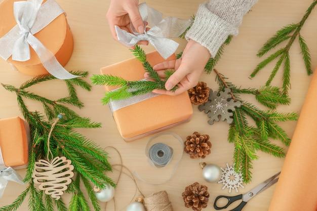 テーブルの上のクリスマスのギフト包装の女性