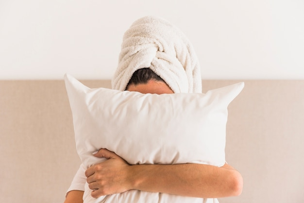 Woman wrapping her head with towel holding white pillow in front of her face