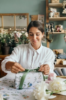 Woman wrapping a present box in flower shop
