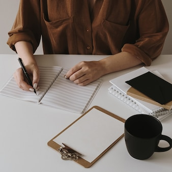 Woman write in a blank sheet notebook. minimalist home office desk workspace with coffee cup, clipboard