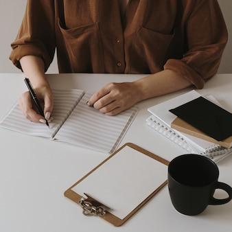 女性は白紙のノートに書きます。コーヒーカップ、クリップボードを備えたミニマリストのホームオフィスデスクワークスペース