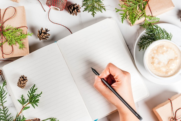 Woman write wishes or to do list in notebook, coffee mug,  gift or present box, decorated with christmas tree branches, pine cones, red berries, on white marble table,  top view