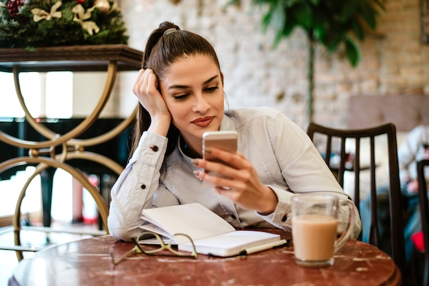 Woman writer using phone while drinking coffee and writing notes.