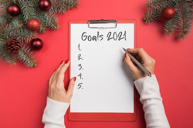 여자는 빨간색에 2021 년 새해의 목표, 체크리스트, 계획을 씁니다.