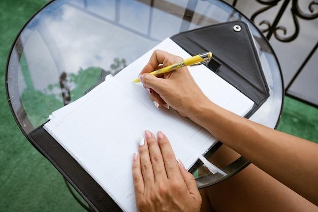 여자는 테라스에서 집에서 테이블에 앉아있는 동안 펜으로 노트북에 씁니다.