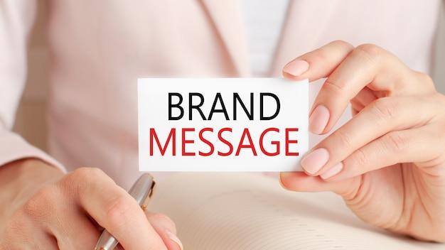 여자는 은색 펜으로 노트북에 쓰고 텍스트가있는 손을 잡아 카드 : 브랜드 메시지